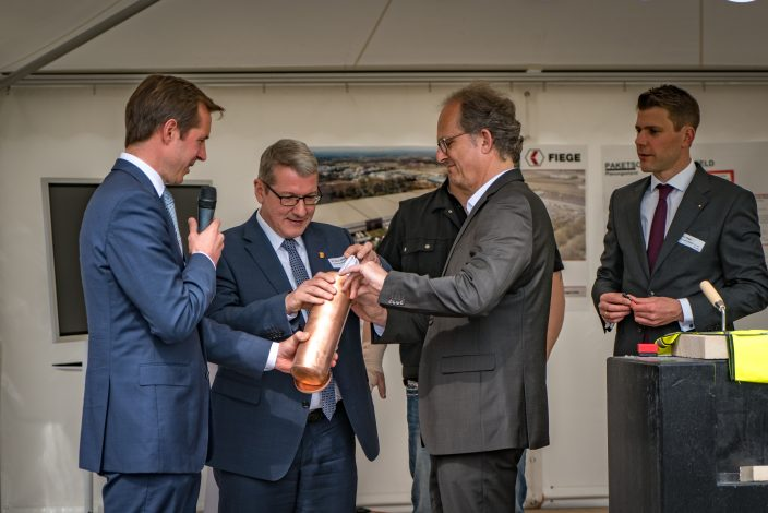 Thomas, Heinicke, head of MediaMarktSaturn logistics in Germany (2nd from right) and the head of the district authority, Dr. Klaus Effing (2nd from left) fill the time capsule.