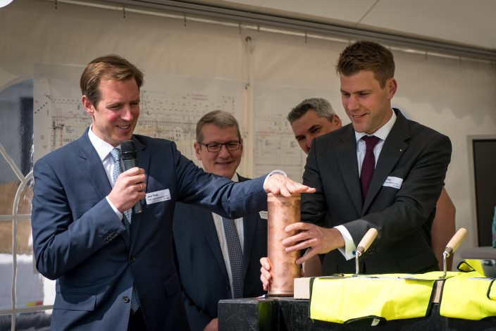 Jens Fiege (left) and Felix Fiege seal the time capsule before it is buried in the foundation stone with a current edition of a daily newspaper, a copy of the Fiege magazine, LOGO, the building's blueprints, and a few coins inside.